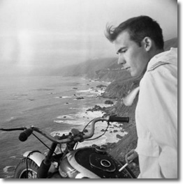 A young Hunter S. Thompson (1937-2005) on his motorcycle at a bluff along the coastline