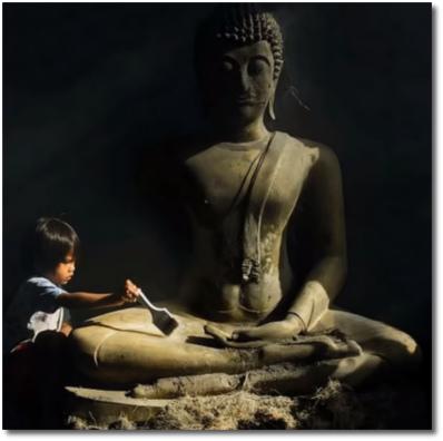 Buddha statue with little boy brushing